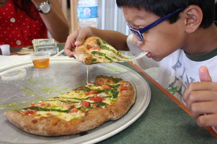 Eshaan eating pizza from Pure Pizza at 7th st public market