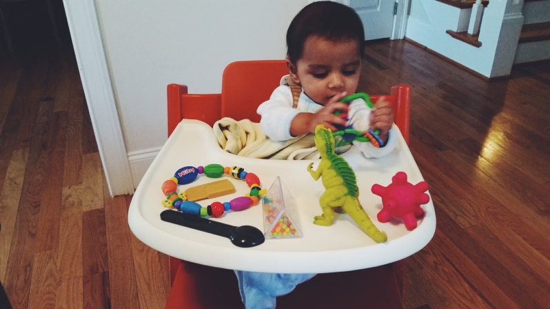 Day at the office - Arjun sitting in high chair and playing with his toys